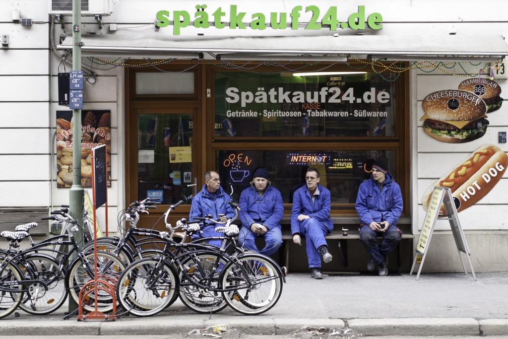 Späti Mitarbeiter auf der Bank vor Kiosk